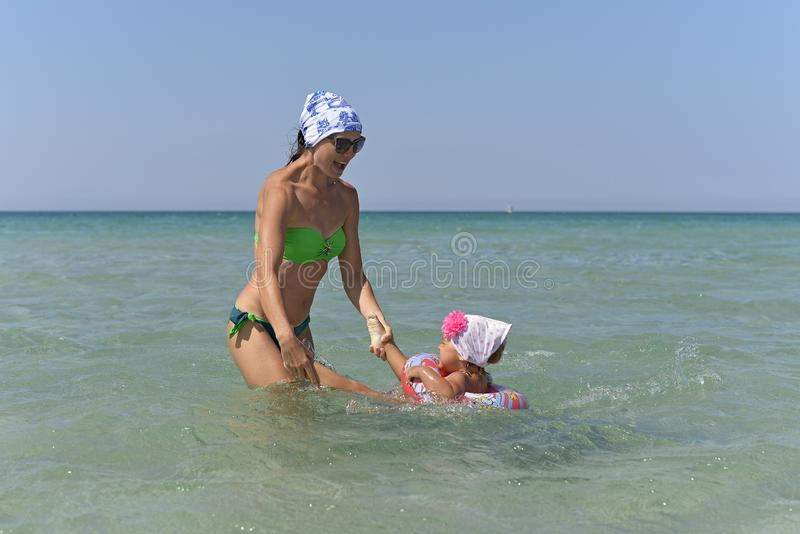 En ung moder med lite dotterbad i havet arkivfoto