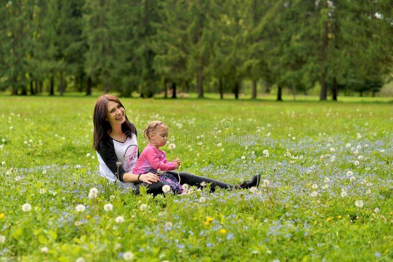 En ung moder med lite dottern som spelar på en grön äng royaltyfria bilder
