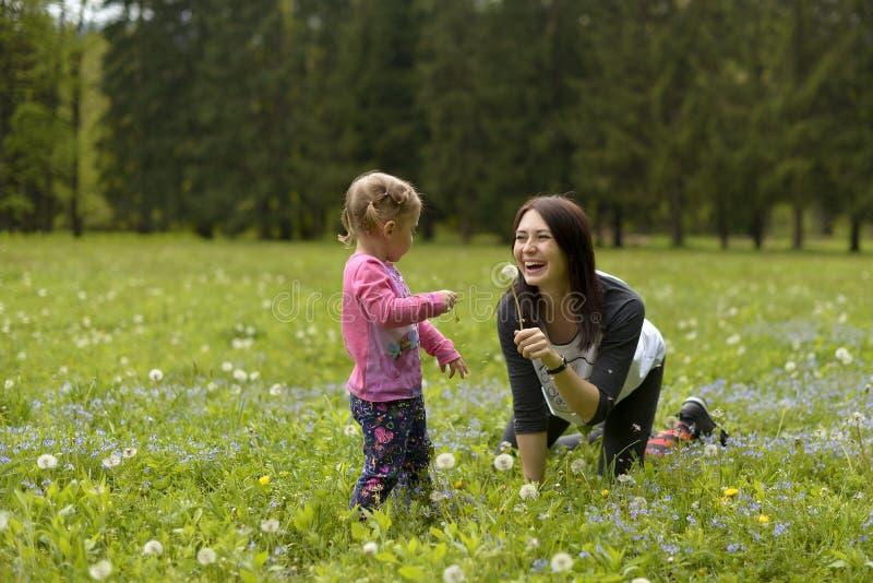 En ung moder med lite dottern som spelar på en grön äng royaltyfri foto