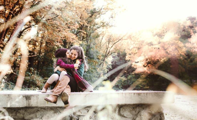 En ung moder med en litet barndotter som kramar och kysser i skog i höstnatur arkivfoto