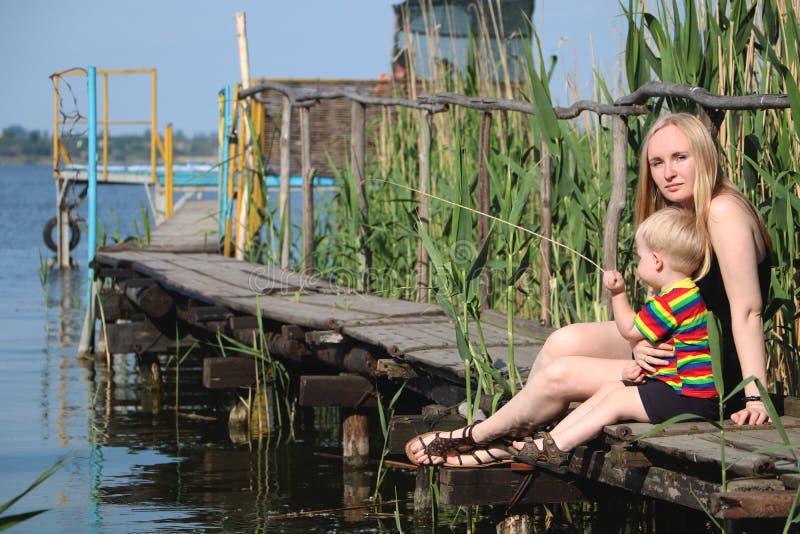 En ung moder och son vilar på bron vid floden Innehåll lutning- och urklippmaskeringen arkivbild