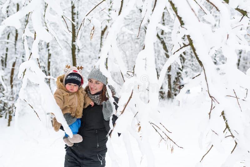 En ung moder rymmer henne behandla som ett barn sonen i henne armar Går i vinterskogen royaltyfri bild