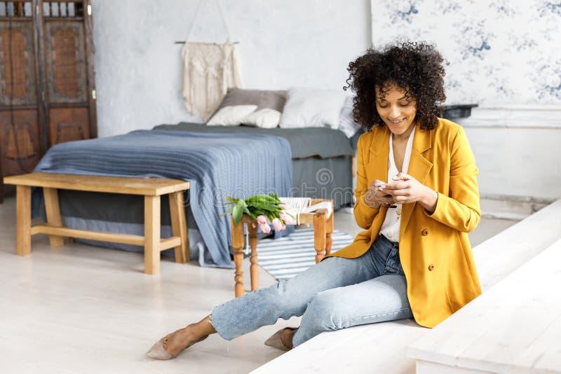 En ung nätt kvinna med lockigt hår som är iklätt ett omslag och jeans som sitter på momenten och ser telefonen arkivbild