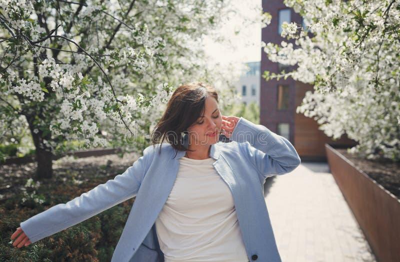 En ung nätt le brunettkvinna med kort hår i ett blått sommarlag dansar i blomstra parkerar med körsbärsröda träd royaltyfri foto