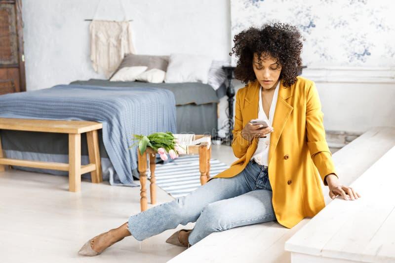 En ung n?tt kvinna med lockigt h?r som ?r ikl?tt ett omslag och jeans som sitter p? momenten och ser telefonen royaltyfri foto