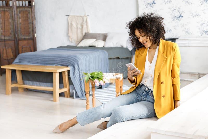 En ung n?tt kvinna med lockigt h?r som ?r ikl?tt ett omslag och jeans som sitter p? momenten och ser telefonen arkivbild