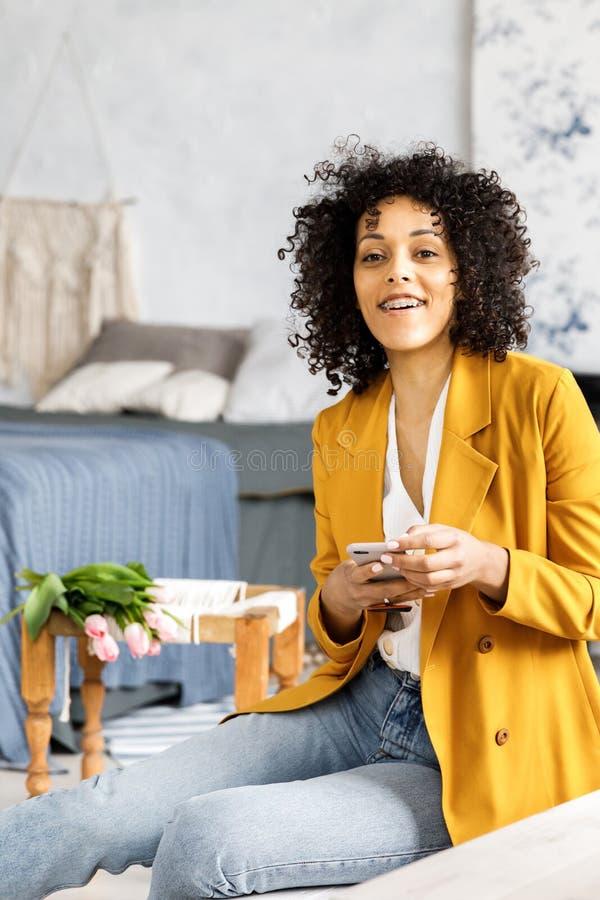 En ung n?tt kvinna med lockigt h?r som ?r ikl?tt ett omslag och jeans som sitter p? momenten och ser telefonen arkivbilder