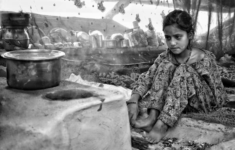 En ung nomad- flicka som förbereder mat för hans föräldrar i en dalfamber av området Anantnag kashmir, Indien arkivbild