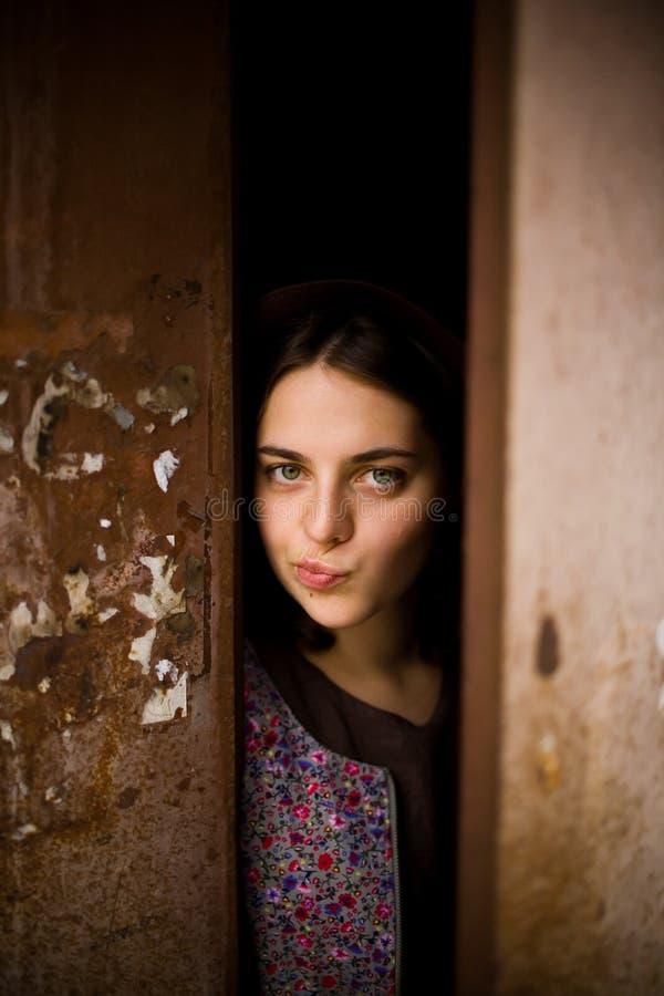 En ung nyfiken flicka ser ut bakifrån dörren av hennes hus Hon tänker om att gå utanför Torgskräckbegrepp arkivfoto