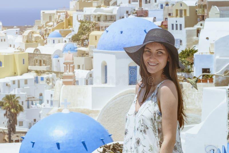 En ung och attraktiv kvinna i en vit klänning och en svart hatt som går på staden av Oia, ö av Santorini, Grekland Begrepp - av arkivbilder