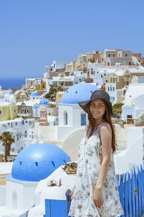 En ung och attraktiv kvinna i en vit klänning och en svart hatt som går på staden av Oia, ö av Santorini, Grekland Begrepp - av arkivfoton