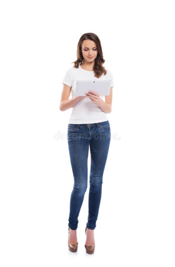 En ung och lycklig flicka i jeans som rymmer en minnestavladator arkivfoto