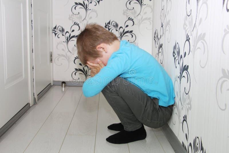 En ung pojke gråter i hallet ensam pojke royaltyfri foto