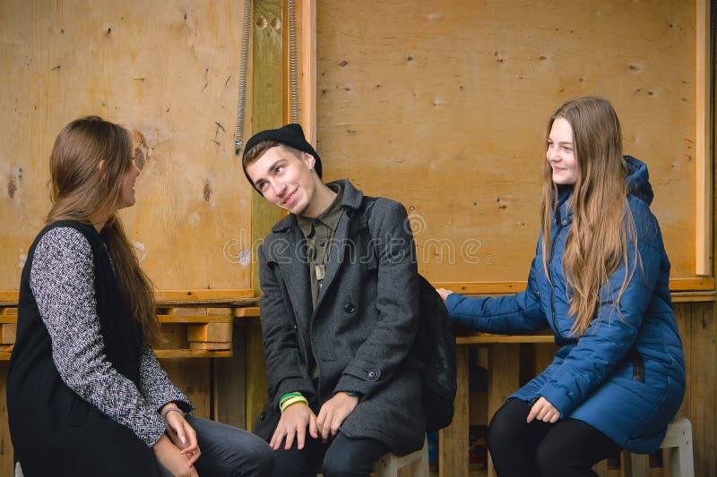 En ung pojke och två flickor som sitter i rummet arkivfoto