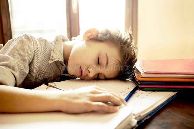 En ung pojke som är stressad på läxa royaltyfri bild