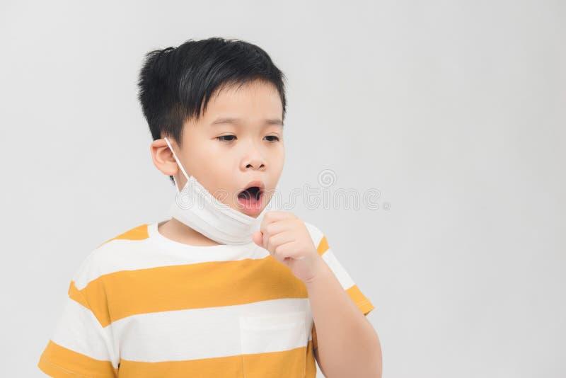 En ung pojke som bär en mask vårdar en förkylning hemma royaltyfri foto