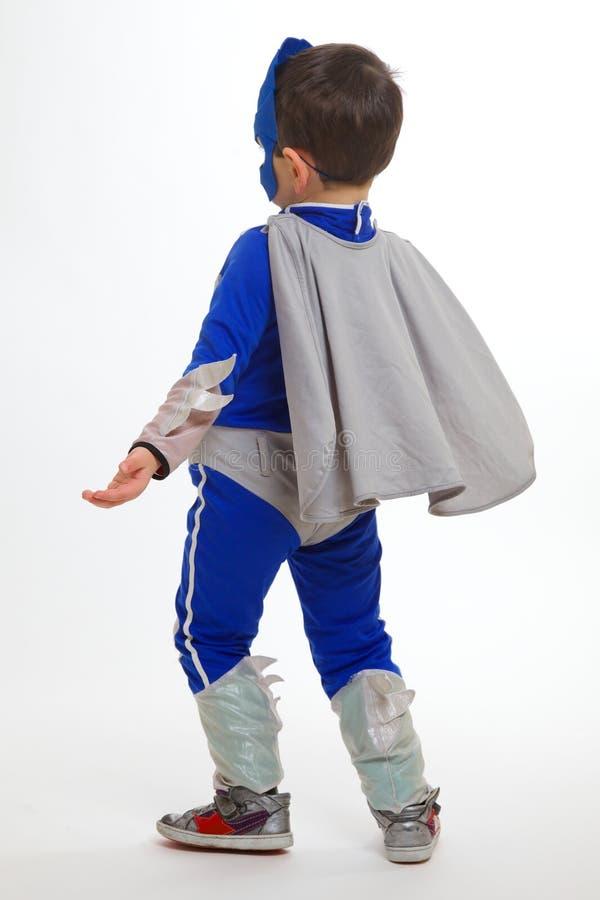 Den unga pojken som ha på sig en superhero, passar vänder mot i väg från kameran arkivfoton