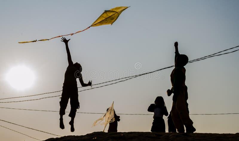 En ung pojke som hoppar upp för flygdraken royaltyfria bilder