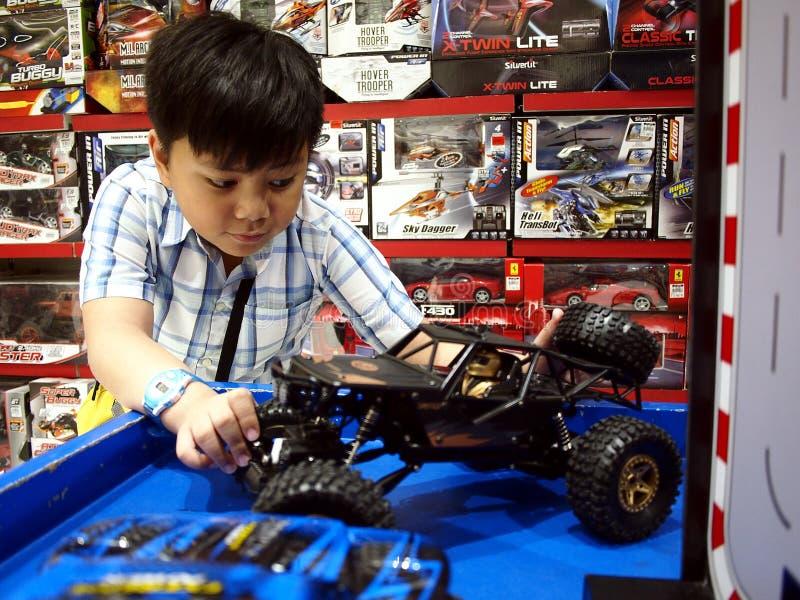 En ung pojke spelar med radion kontrollerade bilar i ett leksaklager arkivfoton
