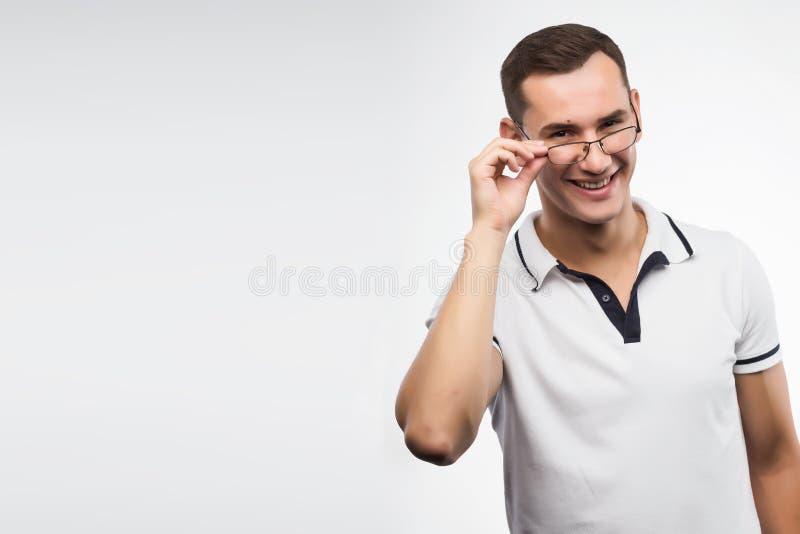 En ung positiv man i glasögon rätar ut hans exponeringsglas med arkivfoto
