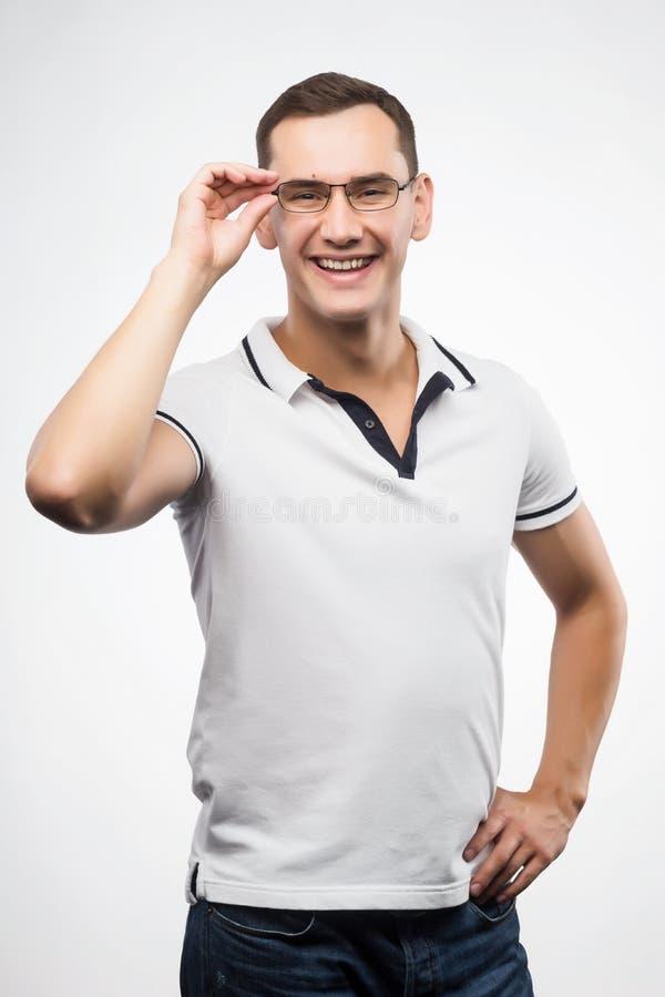 En ung positiv man i glasögon rätar ut hans exponeringsglas med royaltyfria bilder