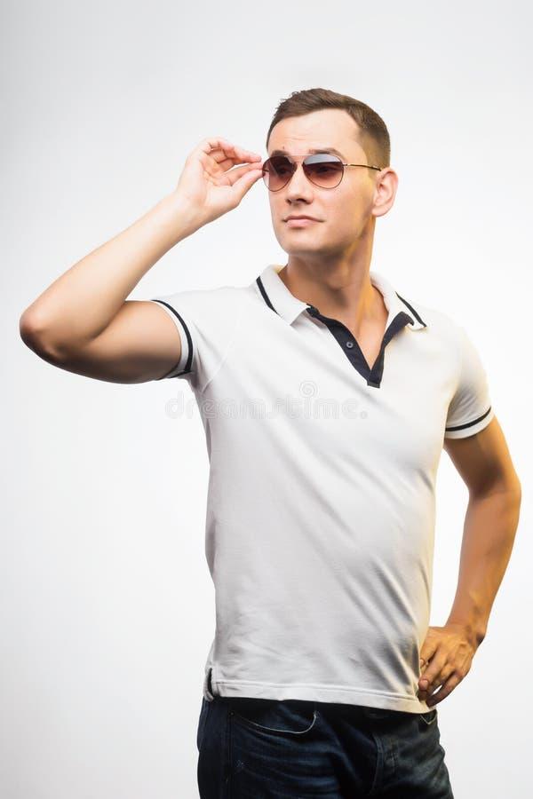 En ung positiv man i solglasögon som tänds av varmt solljus Emotio arkivfoto
