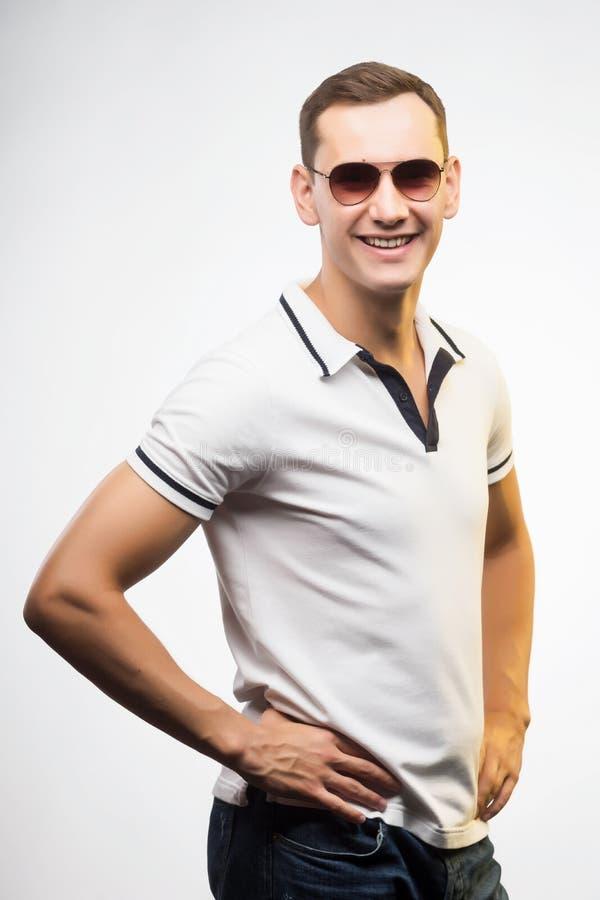 En ung positiv man i solglasögon som tänds av varmt solljus Emotio royaltyfria foton