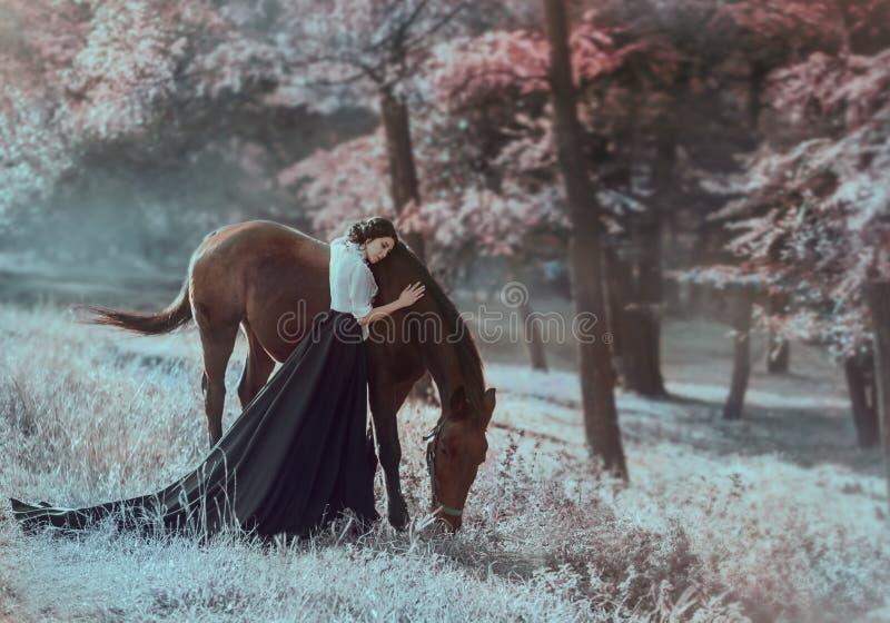 En ung prinsessa i en tappningklänning med ett långt drev, med mjukhet och förälskelse, kramar hennes häst Brunettflickan i en vi arkivfoton