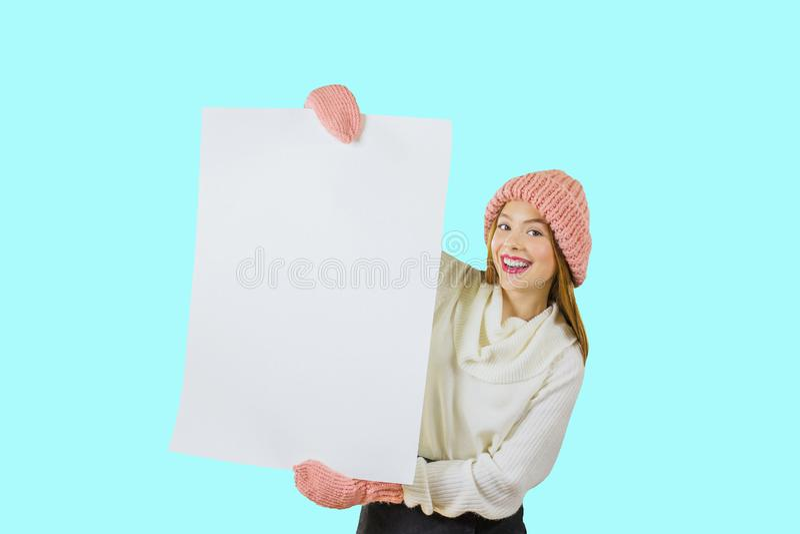 En ung rödhårig flicka i en stucken rosa hatt och tumvanten rymmer en stor affisch av vit färg med båda händer och royaltyfria bilder