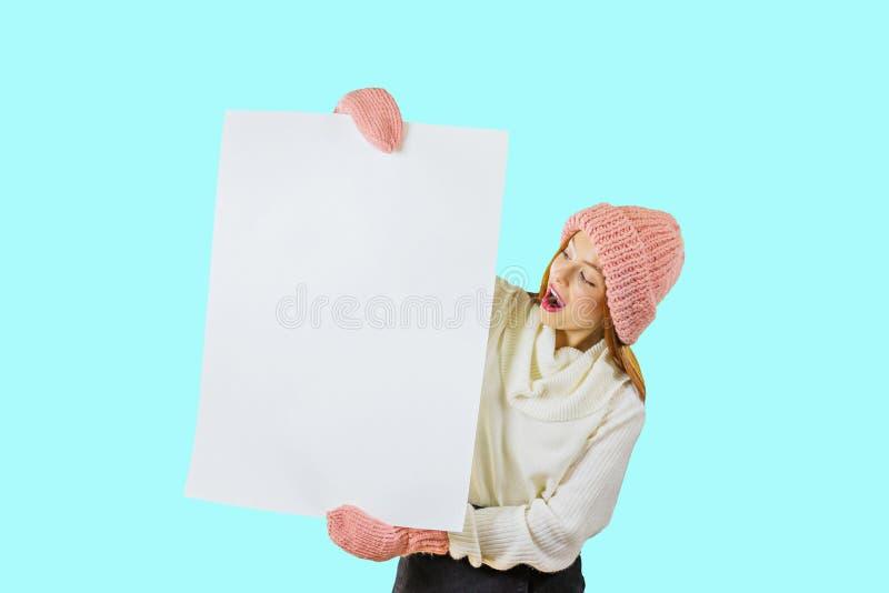 En ung rödhårig flicka i en stucken rosa hatt och tumvanten rymmer en stor vit affisch med båda händer och blickar på royaltyfri fotografi