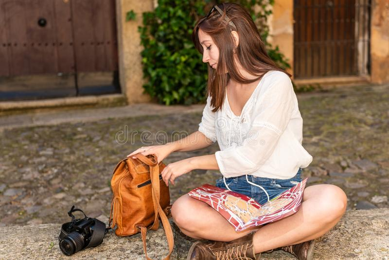 En ung rödhårig turist med en ryggsäck-, kamera- och stadsöversikt vilar i den gamla staden av Caceres royaltyfria bilder
