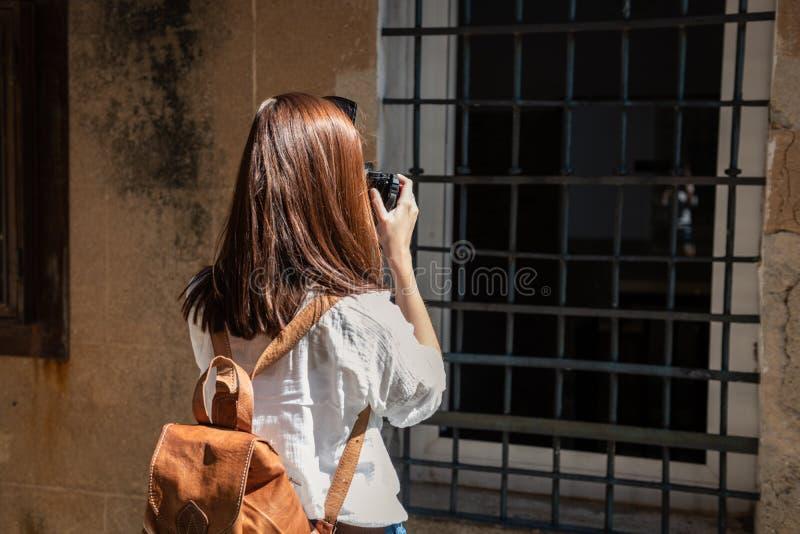 En ung rödhårig turist med en ryggsäck tar fotografier av de smala gatorna av den gamla staden av Caceres arkivfoton