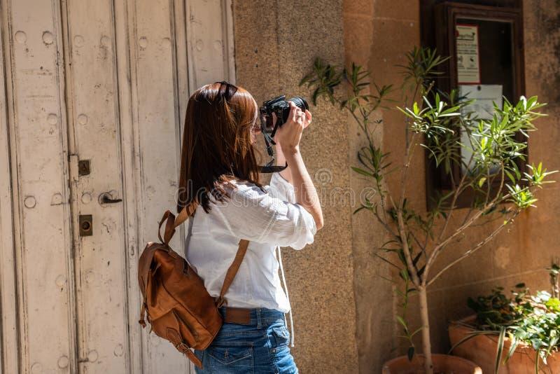 En ung rödhårig turist med en ryggsäck tar fotografier av de smala gatorna av den gamla staden av Caceres royaltyfria bilder