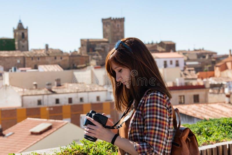 En ung rödhårig turist med en ryggsäck tar fotografier av den gamla staden av Caceres från synvinkeln av Galarza royaltyfri bild