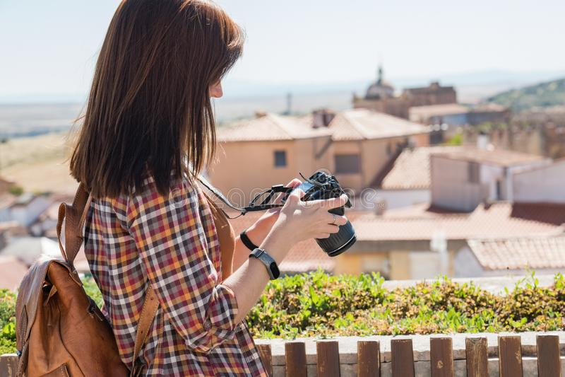 En ung rödhårig turist med en ryggsäck tar fotografier av den gamla staden av Caceres från synvinkeln av Galarza fotografering för bildbyråer