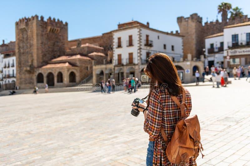 En ung rödhårig turist med en ryggsäck tar fotografier av Plazaborgmästaren i Caceres arkivbild