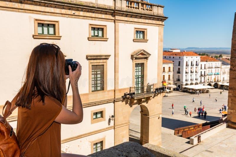 En ung rödhårig turist med en ryggsäck tar fotografier av Plazaborgmästaren i Caceres arkivfoton