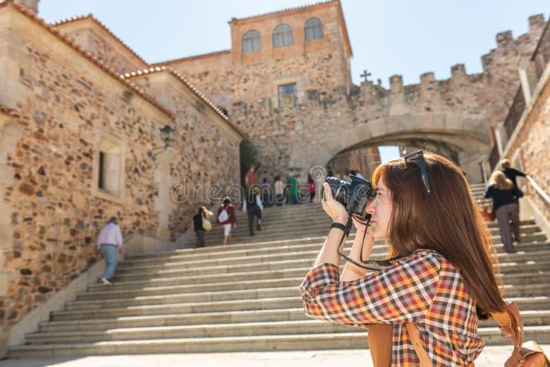 En ung rödhårig turist med en ryggsäck tar fotografier med hennes kamera på momenten av Plazaborgmästaren i Caceres arkivbild