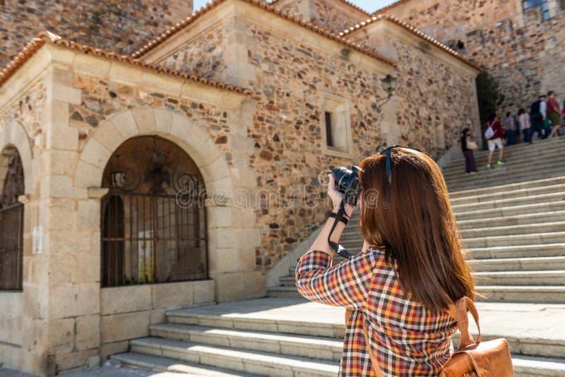 En ung rödhårig turist med en ryggsäck tar fotografier med hennes kamera på momenten av Plazaborgmästaren i Caceres royaltyfri fotografi
