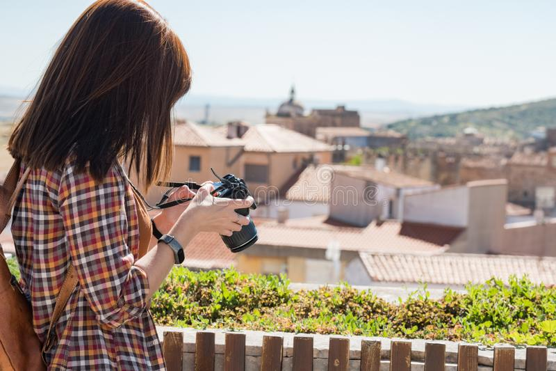 En ung rödhårig turist tar fotografier av den gamla staden av Caceres från synvinkeln av Galarza arkivbild