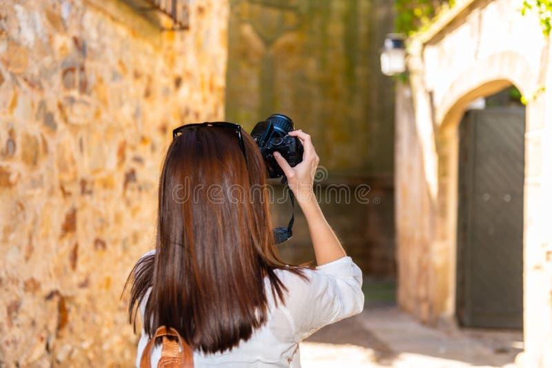 En ung rödhårig turist tar fotografier med hennes kamera av de smala gatorna av den gamla staden av Caceres royaltyfria foton
