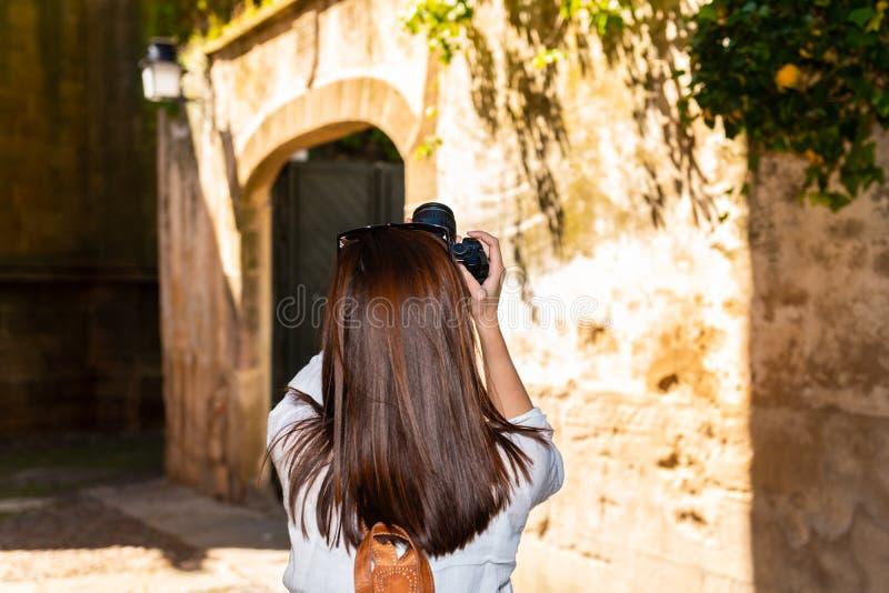 En ung rödhårig turist tar fotografier med hennes kamera av de smala gatorna av den gamla staden av Caceres fotografering för bildbyråer