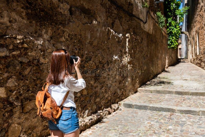En ung rödhårig turist tar fotografier med hennes kamera av de smala gatorna av den gamla staden av Caceres royaltyfri foto