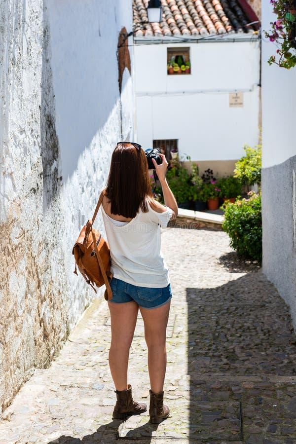 En ung rödhårig turist tar fotografier med hennes kamera av en gränd i den gamla judiska fjärdedelen av Caceres royaltyfri fotografi
