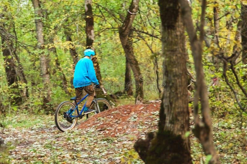 En ung ryttare som kör en mountainbike, rider på hastighet som är sluttande i höstskogen royaltyfri fotografi