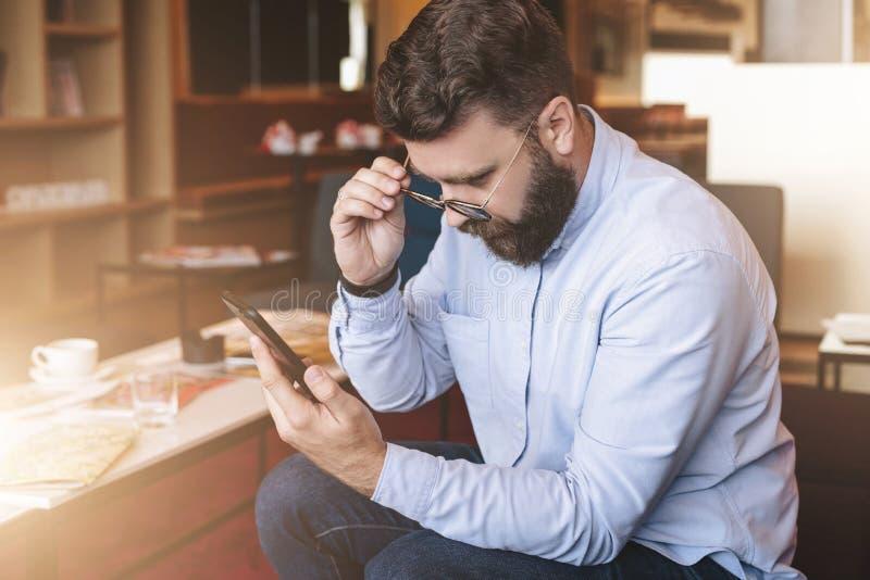 En ung skäggig affärsman sitter på en soffa i hotelllobbyen och ser smartphoneskärmen som fäller ned hans exponeringsglas royaltyfria foton