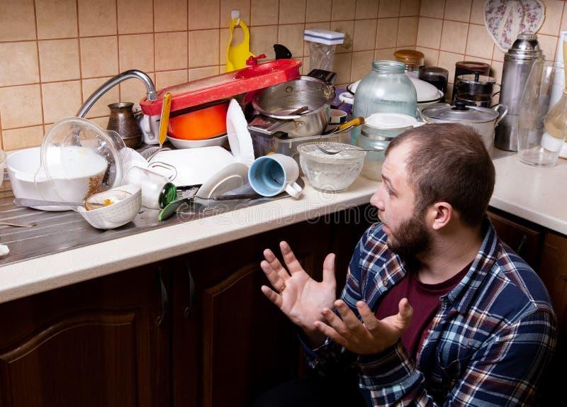 En ung skäggig grabb sitter på golvet och chockas av beloppet av smutsig disk som ligger i diskhon som ska tvättas arkivbilder