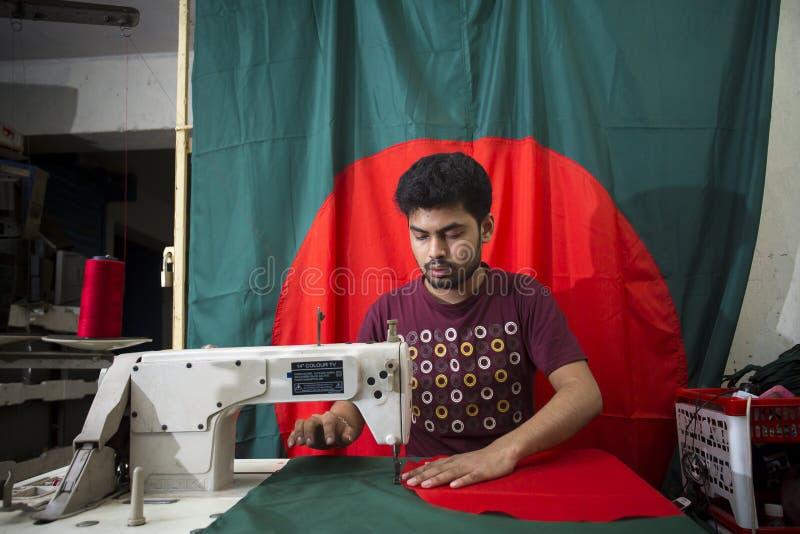 En ung skräddare Md Rashed Alam åldras 28 bangladeshiska nationsflaggor för danande på Dhaka, Bangladesh arkivbilder