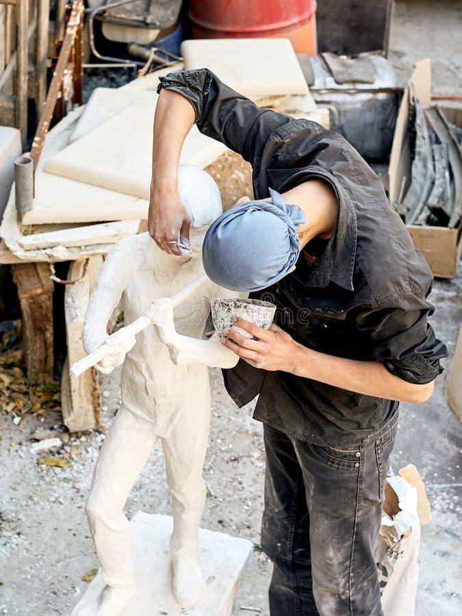 En ung skulptör i en bandana gör en skulptur av en pojke som spelar flöjten royaltyfri bild