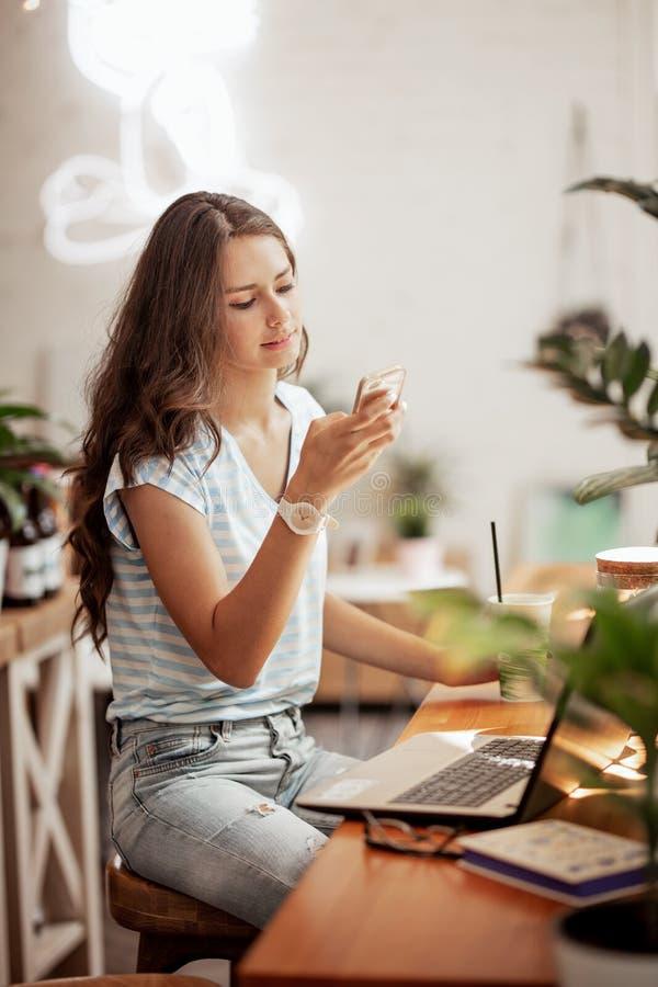 En ung slank flicka med långt hår, bärande tillfällig stil, sitter på tabellen med en bärbar dator och ser hennes telefon i en sl royaltyfri foto